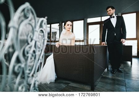 Beautiful wedding photo, bride and bridegroom at big window background, black and white.