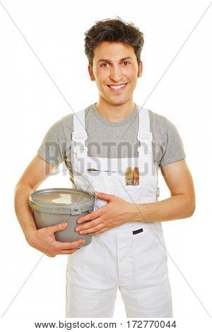 Smiling painter with white overall carrying a paint bucket in his hands