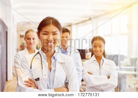 Happy doctor with team of nurses at hospital