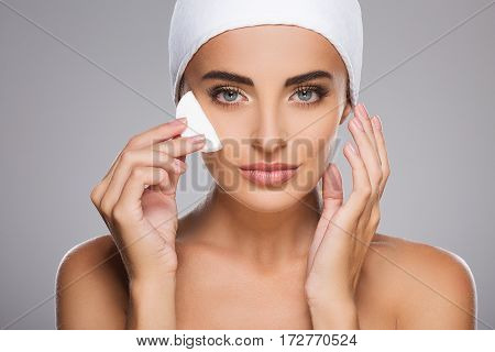 Perfect girl with brown hair fixed behind, clean fresh skin, big eyes and naked shoulders wearing white bandage, posing at gray studio background with cleaning sponge near face, close up.