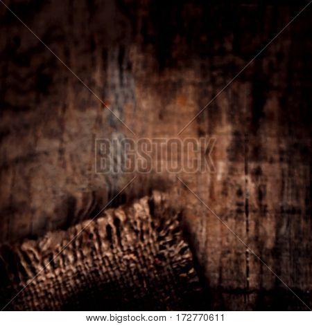 Old wooden table with sack cloth in dark interior with copy space. Burlap texture