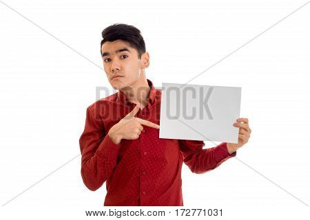 youn funny brunette male model in red shirt posing with empty placard in his hands and looking at the camera isolated on white
