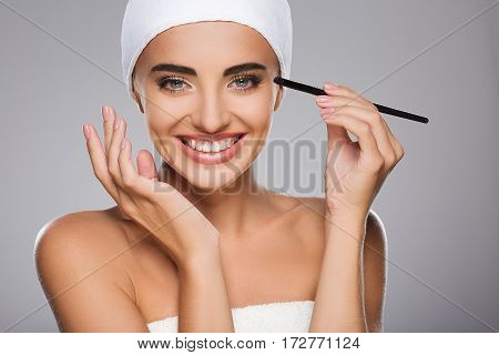 Smiling girl with brown hair fixed behind, clean fresh skin, big eyes and naked shoulders wearing white bandage, doing make up at gray studio background, portrait.