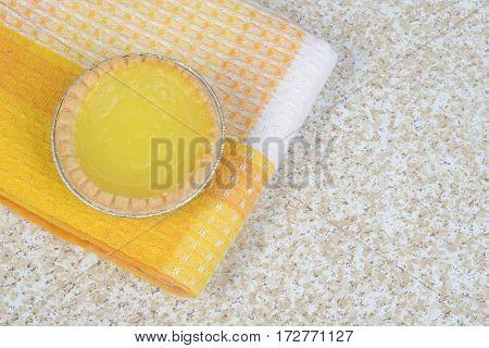 top view of lemon tart on yellow napkin