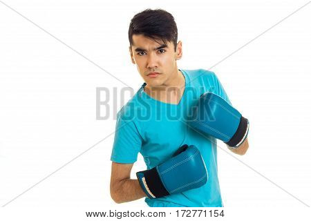 portrait of serious brunette boxer sportsman in blue gloves looking at the camera isolated on white