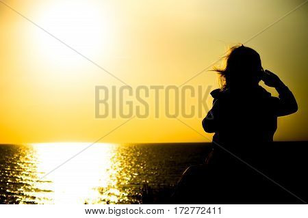 The child on sea background with the setting sun on the horizon