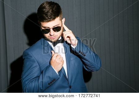 Young man in sunglasses wearing suit with bow. Serious man, imitating connection through earphone like spy. Waist up, studio, indoors
