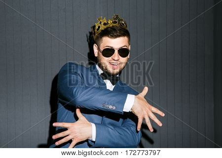 Man in sunglasses wearing suit with bow and crown on head. Feeling good, hands crossed. Cool gesture. Cool, fancy look. Waist up, studio, indoors