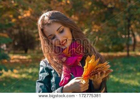 girl smiling keeps the leaves drooping head in the Park