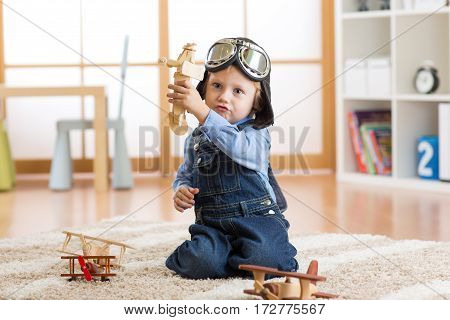 Pilot aviator child boy plays with wooden toy airplanes on floor in his room