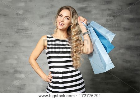 Woman with shopping bags on light background
