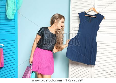 Young woman with shopping bags in dressing room