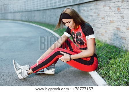 Pain in leg, sport injury. Girl  in orange and black training suit sitting on ground, feeling pain in leg, painful trauma. Full body, profile, closeup, looking down. Outdoors, stadium