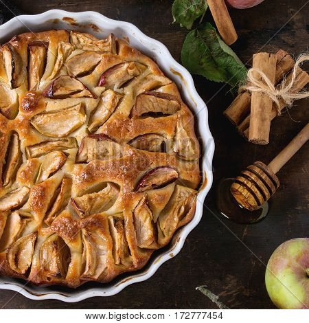 Homemade apple cake pie in white ceramic form with fresh apples with leaves, honey and cinnamon sticks over dark wooden background. Top view