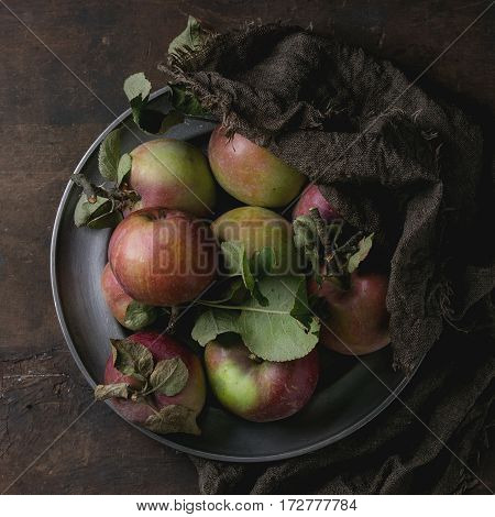 Vintage metal plate with harvest of wild apples with leaves on sackcloth rag over old wooden background. Top view, dark rustic style