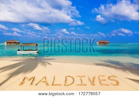 Word Maldives on beach - concept holiday background