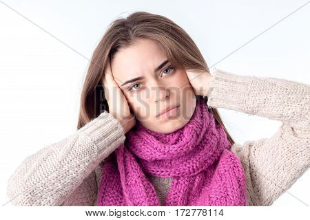 girl in a warm scarf cocked her head and kept her hands isolated on white