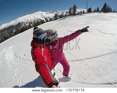 Skier couple on snowy mountainside show something in distance