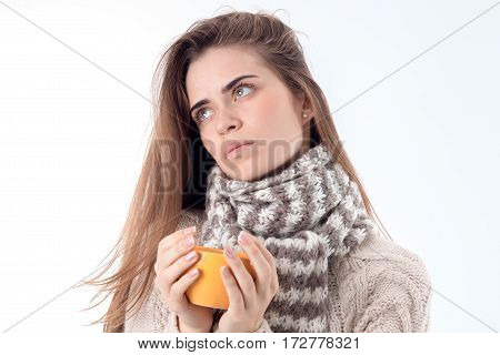 a girl in a scarf and jacket looks into the distance and holding a cup isolated on white