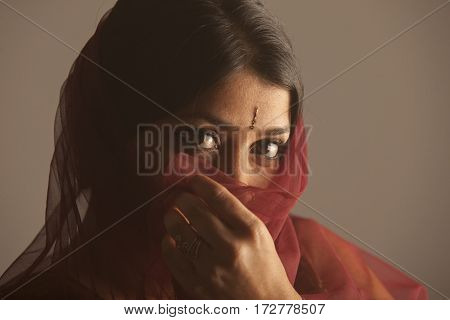 portrait of a shy brunette indian woman with dark skin hiding her face with a colorful scarf