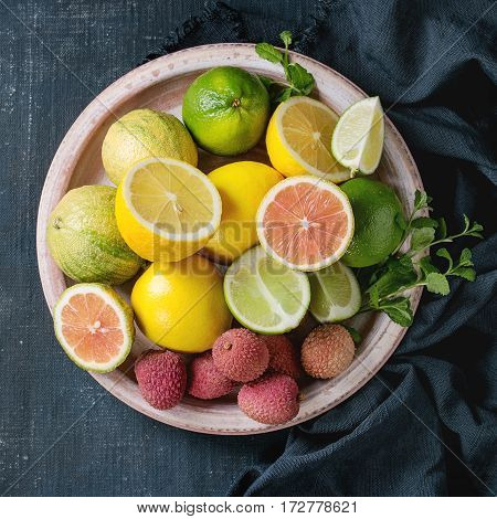 Variety of whole and sliced citrus fruits pink tiger lemon, lemon, lime, mint and exotic lichee on plate with textile over dark blue canvas textured background. Top view with space. Healthy eating