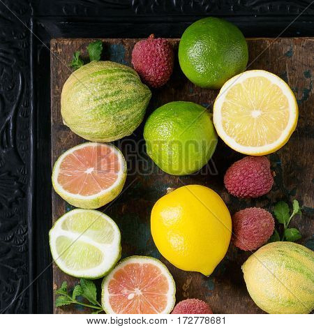 Variety of whole and sliced citrus fruits pink tiger lemon, lemon, lime, mint and exotic lichee over dark ornate and old wooden background. Top view with space. Healthy eating