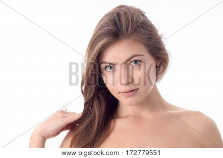 young girl without makeup looks straight close-up in studio