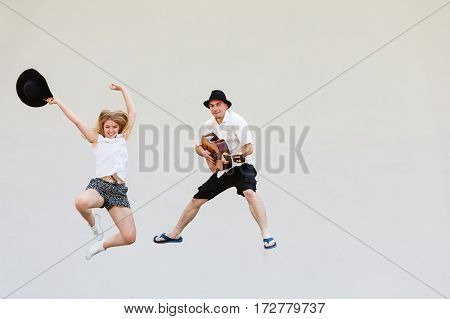 Relationship goals concept. Couple on romantic date. Man with guitar and woman jumping