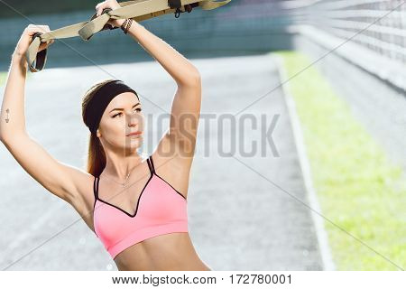 Sport, exercises with training loop outdoors. Girl in rose top doing exercises with training loop on stadium. Sporty girl in good shape looking aside, waist up, closeup, front view