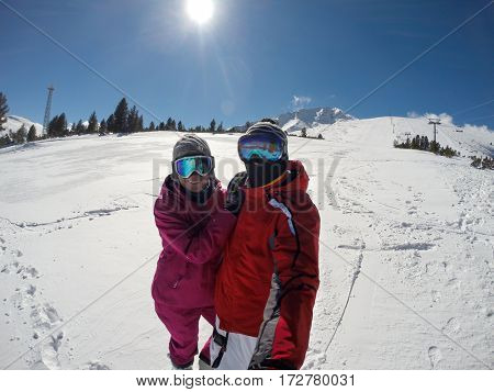 Young skiers couple on white skiing terrain