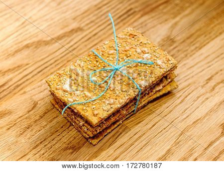 Delicious crispbread tied with organic blue thread on wooden oak table