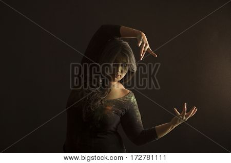 Portrait of indian woman dancing and covered in colored dust isolated in black background