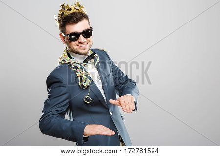 Stylish young man in suit with bow and sunglasses. Wearing crown, confetti on shoulders. Feeling good, smiling. Outrageous, fancy look, cool. Waist up, studio, indoors