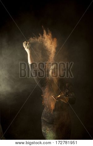 Indian woman dancing and throwimg colored dust in the air