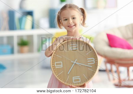 Cute little girl with big clock at home