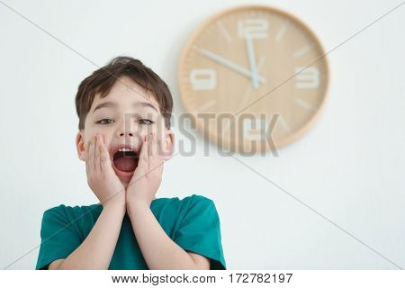 Cute little boy and wall with big clock on background