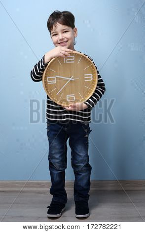 Cute little boy with big clock at home