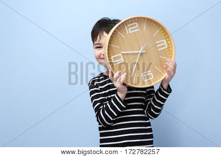 Cute little boy with big clock on color background