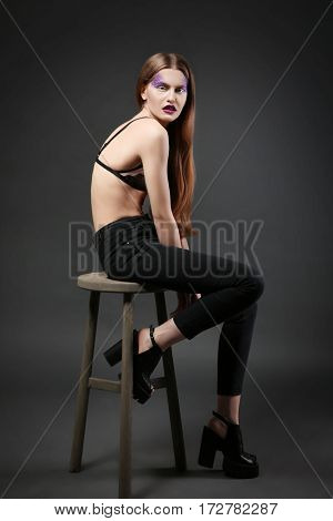 Young model with creative makeup on dark background