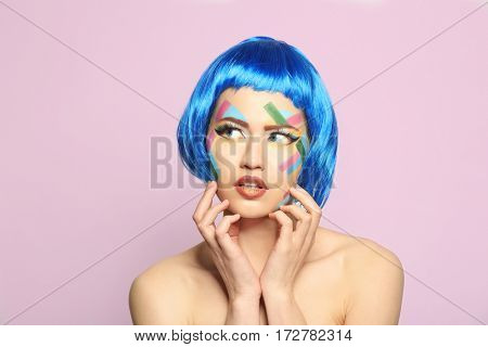 Portrait of young woman with creative make up and blue hair on light background