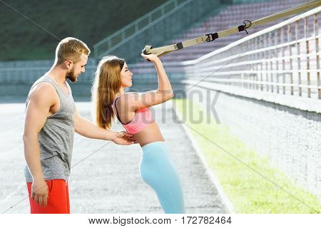 Sport, exercises with training loop outdoors. Girl in rose top and blue leggins doing exercises with training loop on stadium. Coach making corrections, helping with exercises. Profile, closeup