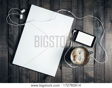 Photo of blank stationery template on vintage wooden table background. Responsive design template. Paper blank letterhead coffee cup smartphone and headphones. Top view.
