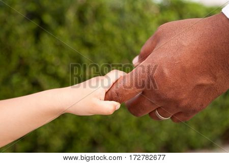 Multicultural family. Father and son holding hands.
