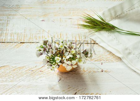 White field flowers in eggshell white napkin green grass twig on wood surface in soft morning sunlight Easter decorationmother's day greeting card template