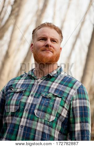 Portrait of red haired man with plaid shirt and long beard in the forest