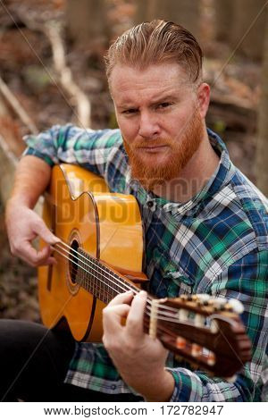 Hipster man with red beard playing a guitar in the field