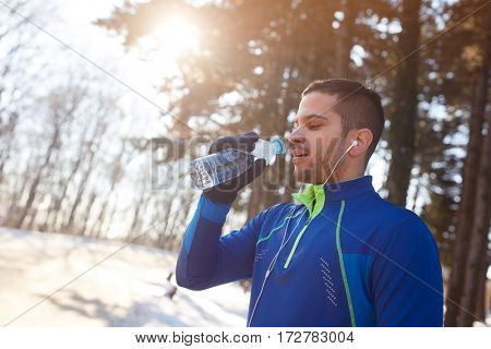Male runner on break  of training with bottle of water outdoor