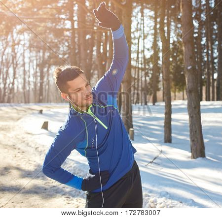 Young male exercises in forest in winter
