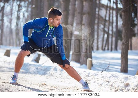 Male jogger worming up legs after training in park