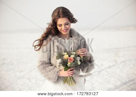 Beautiful bride with bouquet outdoors on winter day